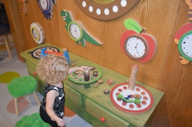 Working at the Clock Factory. She's having fun stacking the pieces.